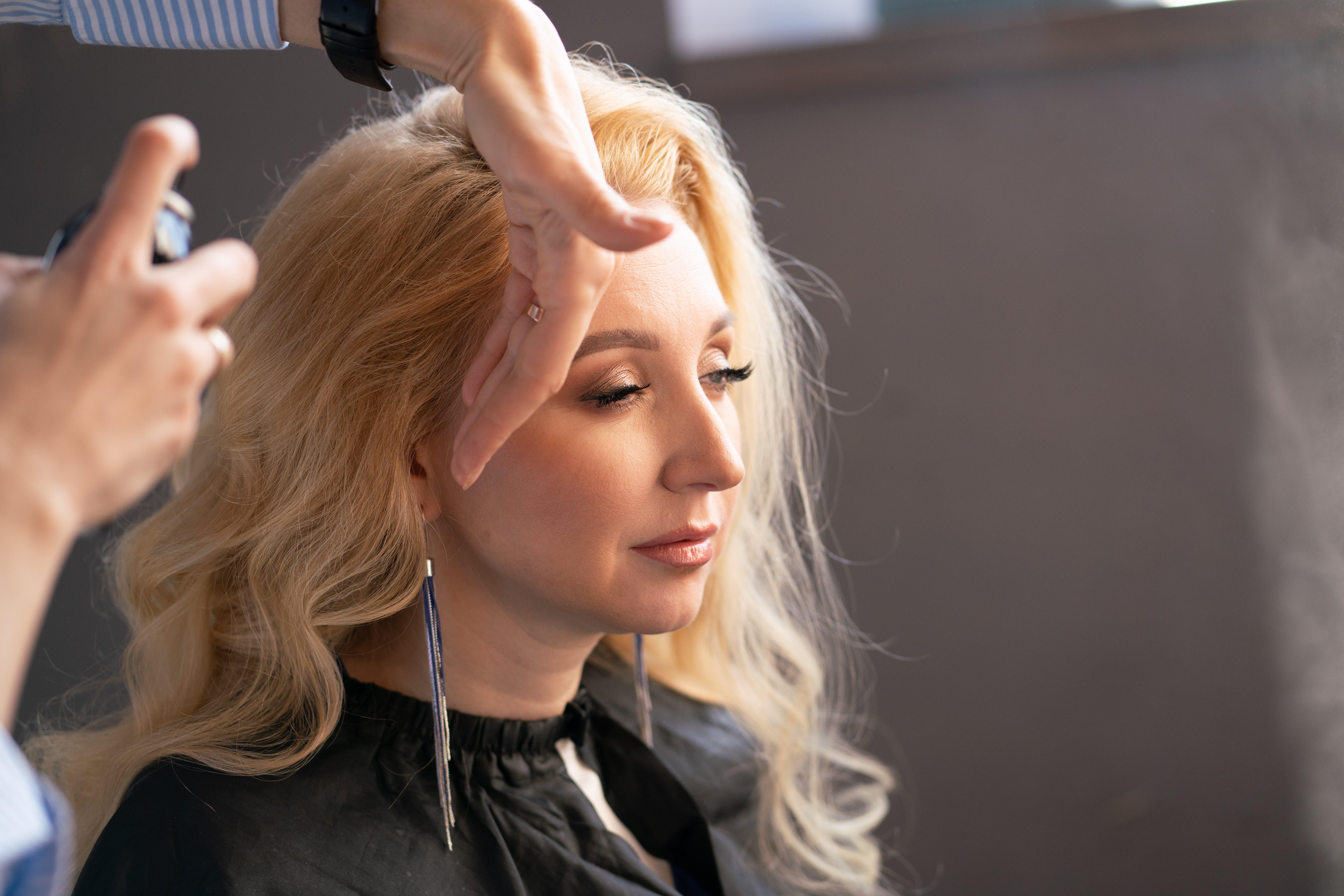 Peluquera arregla el cabello de la mujer. Fuente: Shutterstock