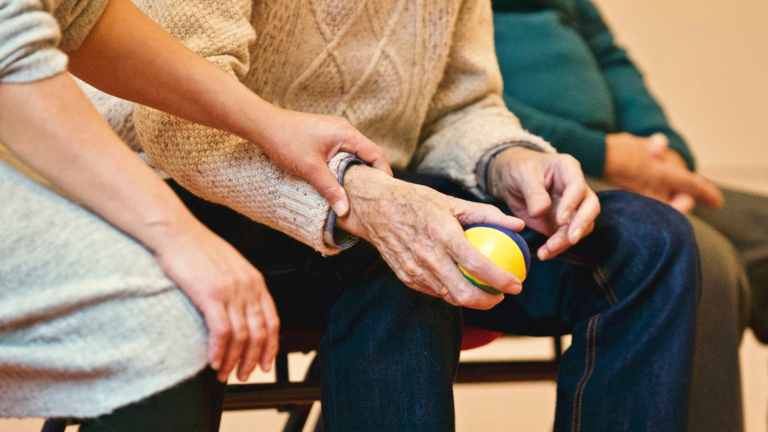 A woman wearing a gray outfit holding the arm of an elderly man who holds a stress ball in his hand   Source: Pexels