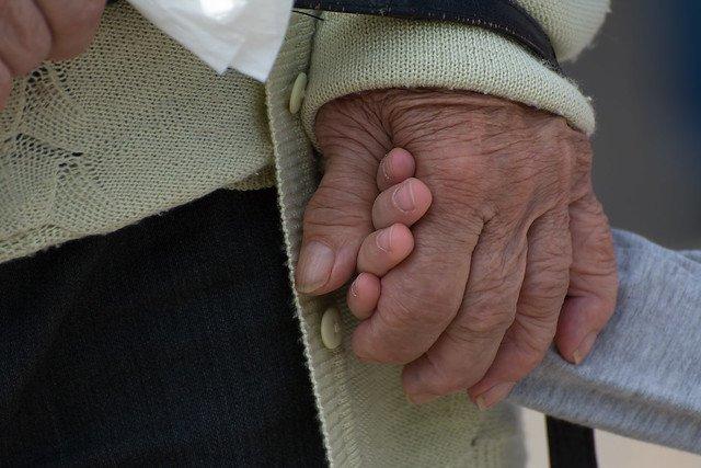 Une personne âgée tenant la main d'un enfant. l Source: Flickr