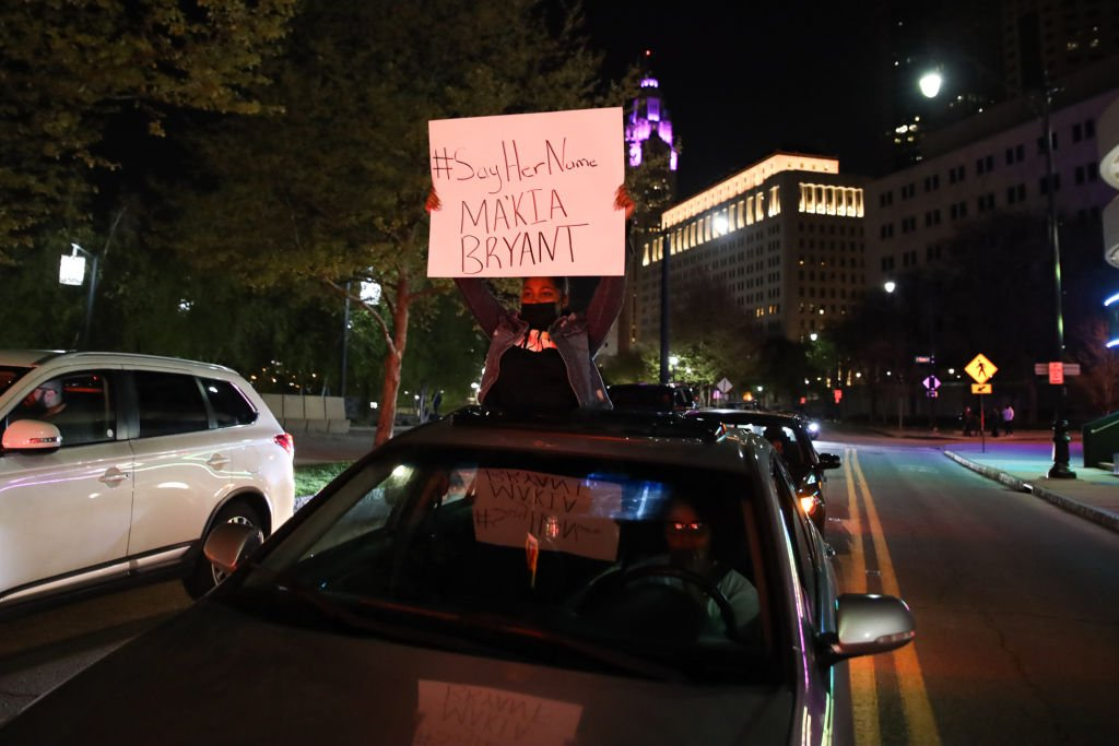 A protester holds a sign out of a car during the MaKhia Bryant protest on April 21, 2021 | Photo: Getty Images