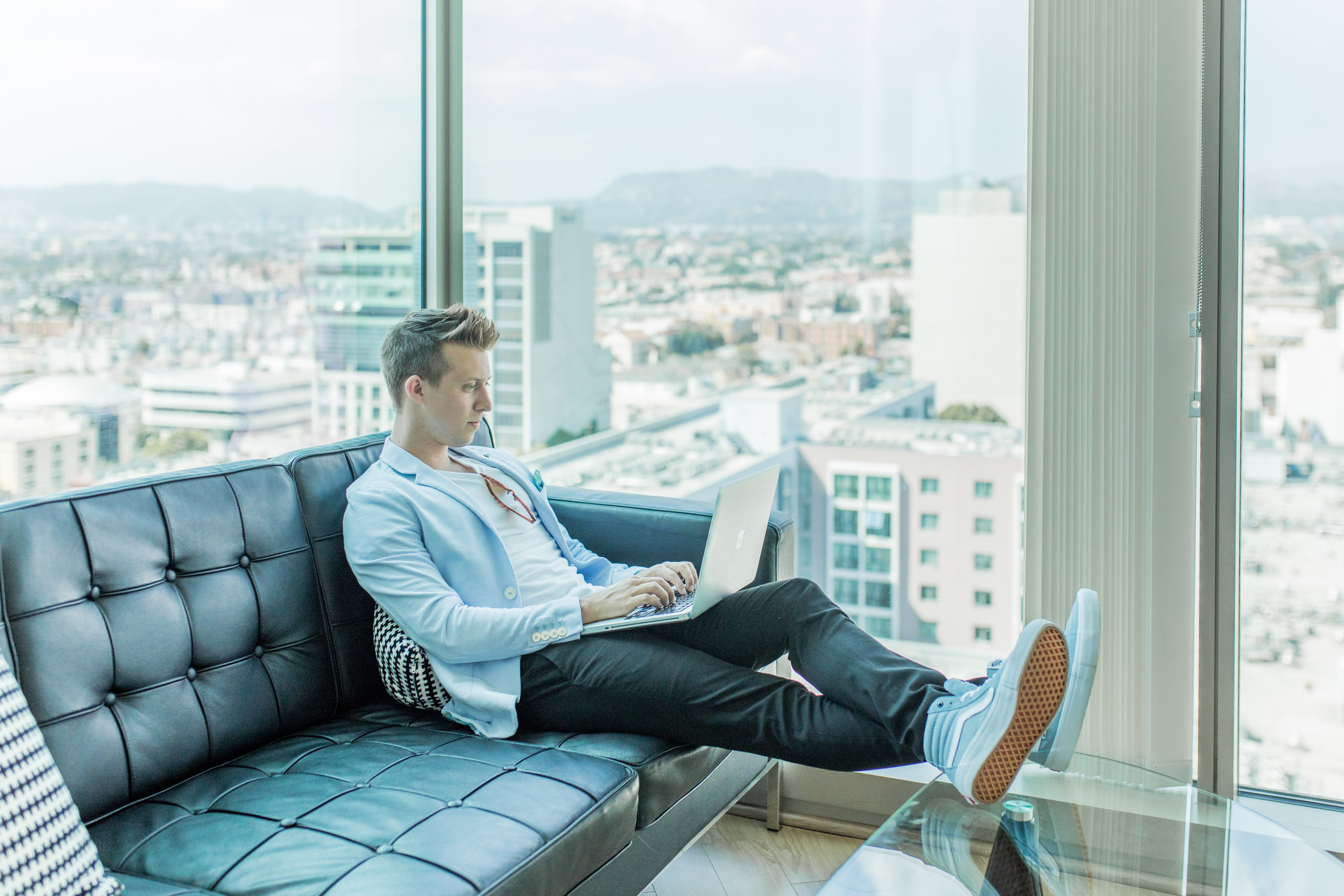 Man sitting on a sofa with a laptop | Source: Unsplash