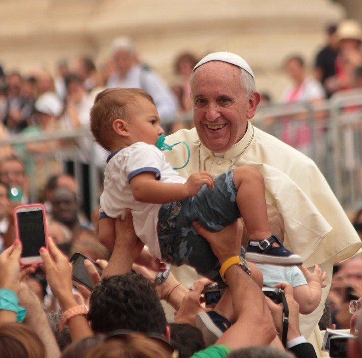 A picture of the Pope holding a child in the midst of the crowd. | Photo: Pixabay