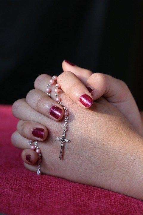 Mujer joven orando con un rosario entre sus manos. | Imagen: Pixabay