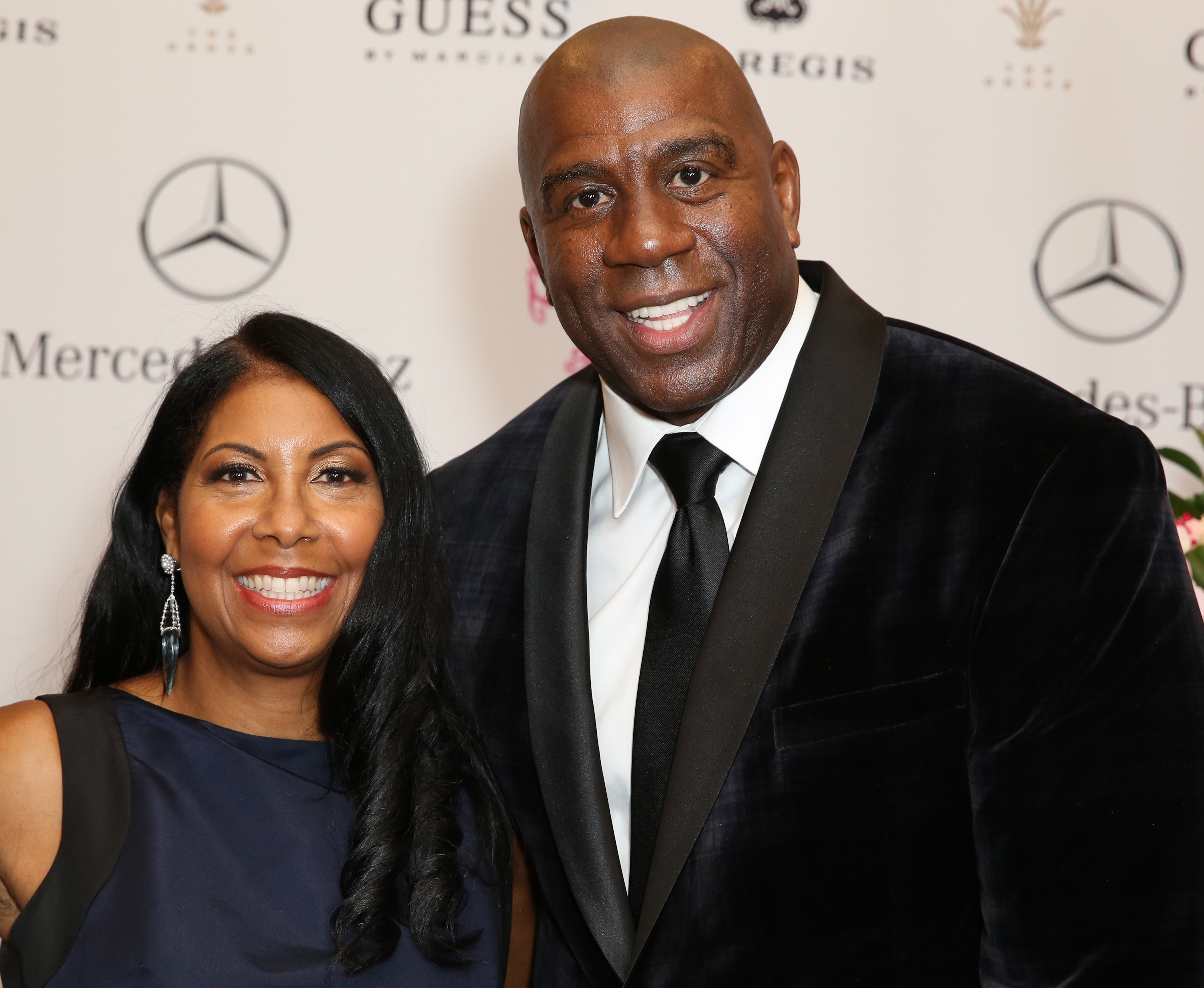 Magic and Cookie Johnson looking regal in black at a Mercedes Benz event held in Beverly Hills, California on October 11, 2014. | Photo: Getty Images.