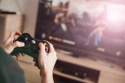 Jeune homme jouant à un jeu sur une console vidéo.   Source : Shutterstock.