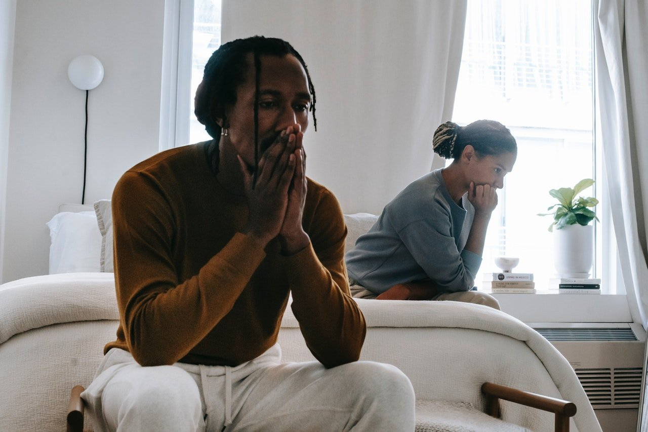Worried husband and wife sitting on a bed   Source: Pexels