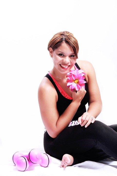 Une femme contente avec une fleure.   Photo : Pixabay