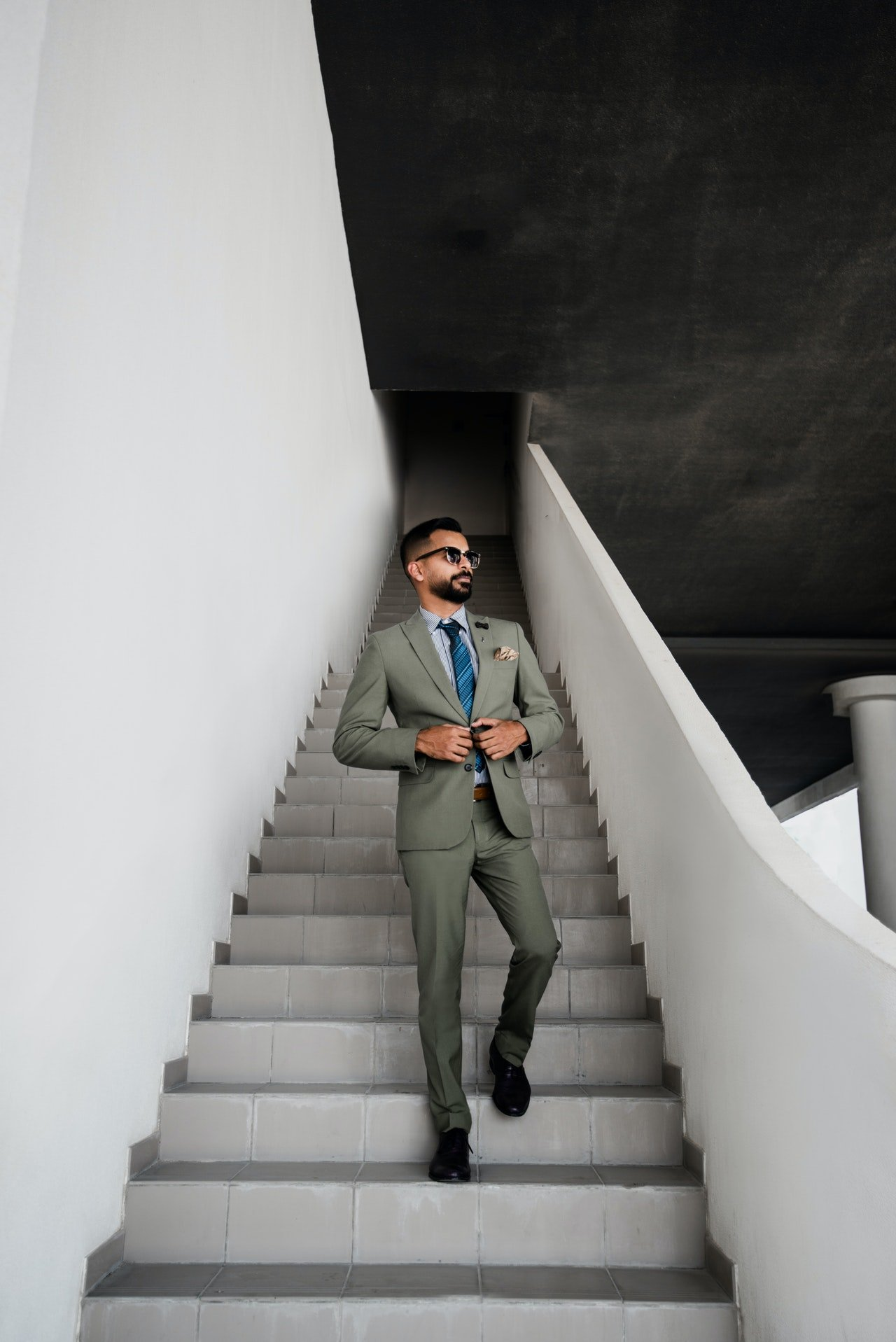 A man in grey suit standing on a staircase   Photo: Pexels