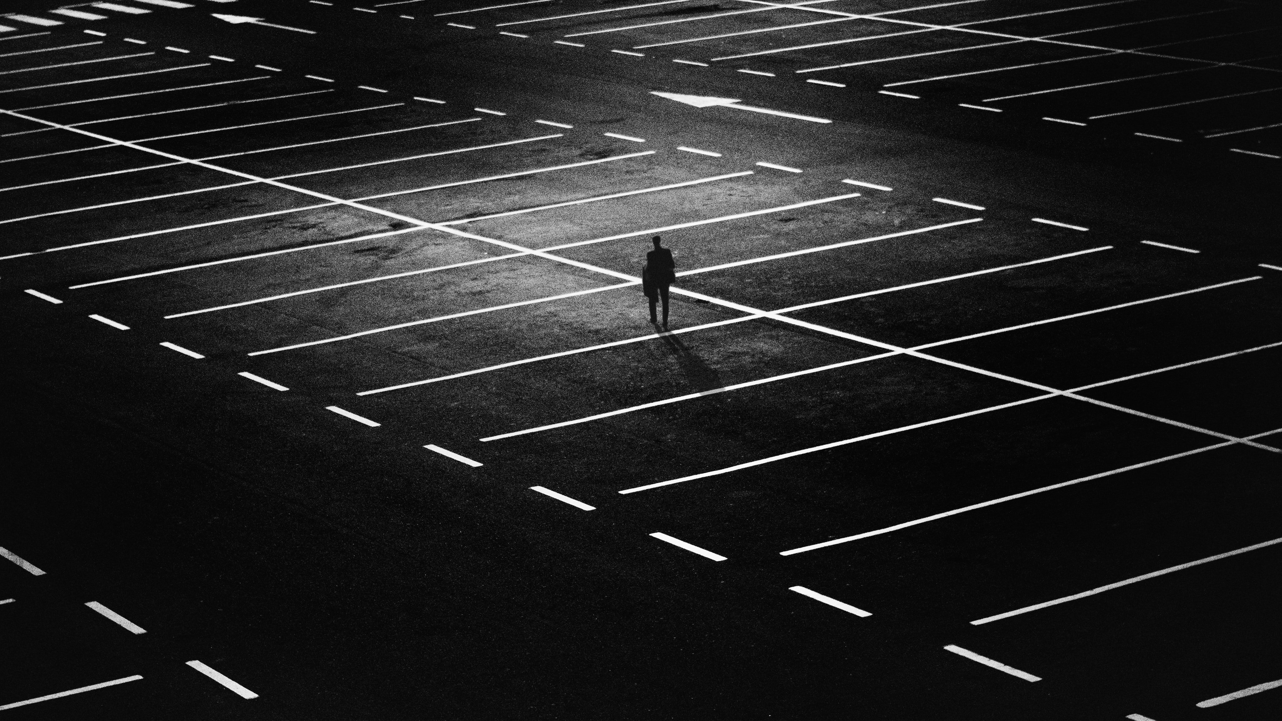 Pictured - A man standing on an empty parking lot   Source: Pexles