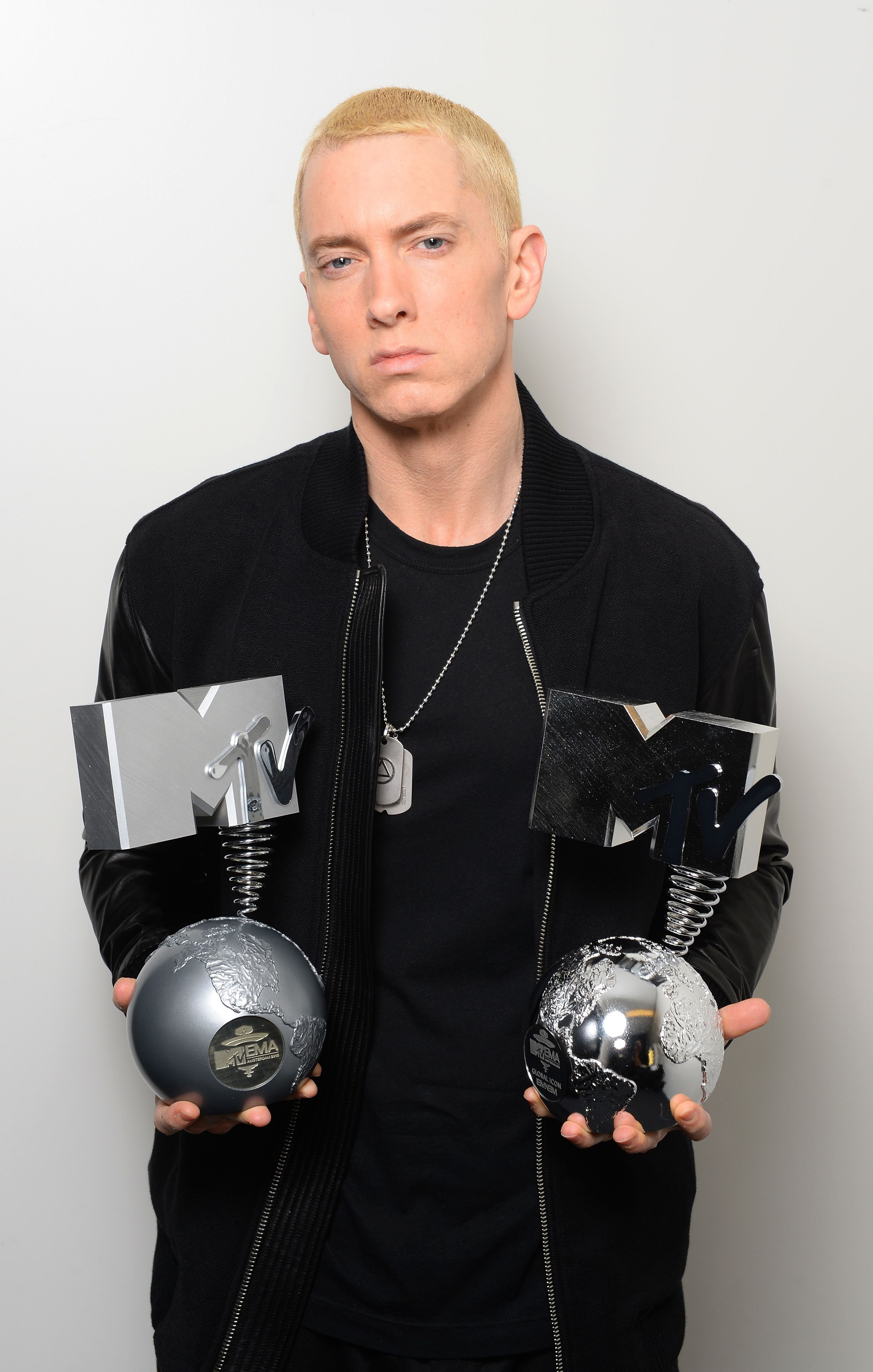 Eminem poses in his dressing room with the 'Best Hip Hop' and 'Global Icon' awards during the MTV EMA's 2013 at the Ziggo Dome on November 10, 2013 | Photo: Getty Images