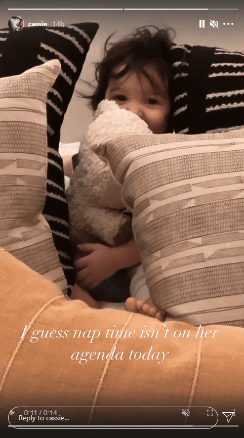 Cassie's daughter Franke Fine peaks out from behind pillows holding a teddy bear.   Source: Instagram/cassie