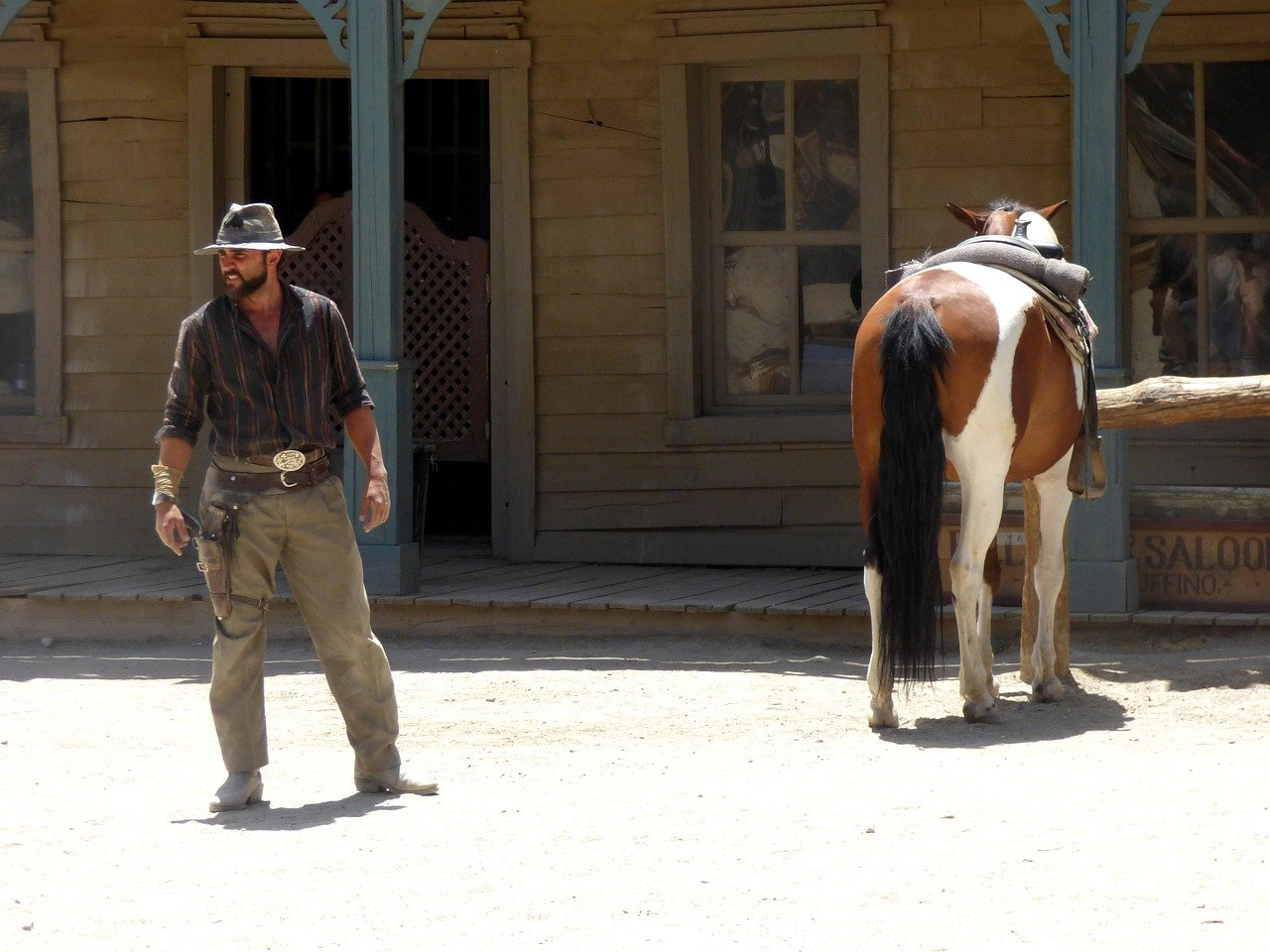 A cowboy looking confused as he looks around with a horse close by   Photo: Pixabay/Pashi