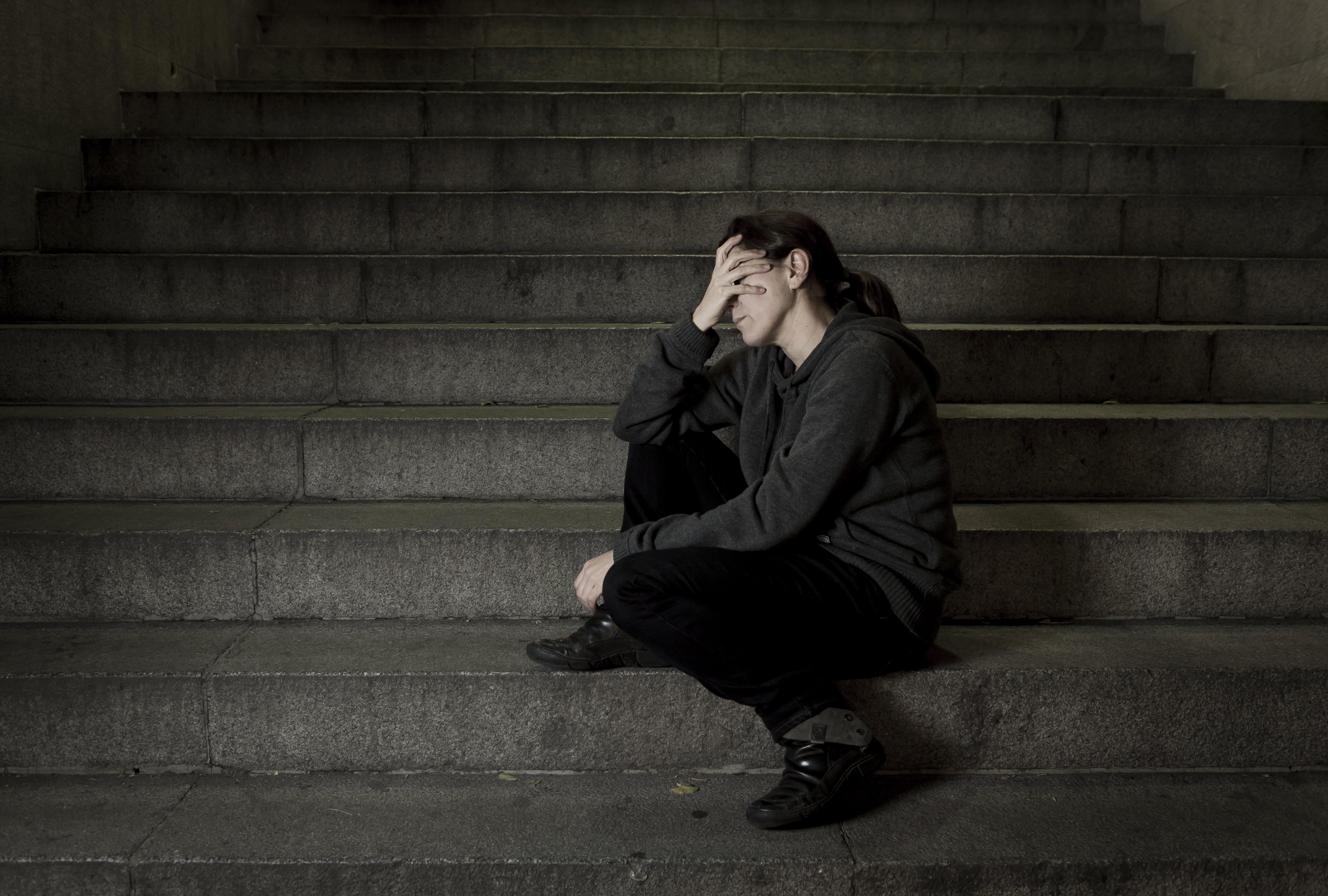 Une femme seule et triste dans l'escalier du métro de la rue | Photo : Shutterstock