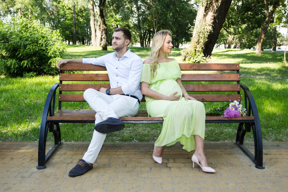 A pregnant wife and husband on a bench in the park, having a quarrel.   Photo: Shutterstock.