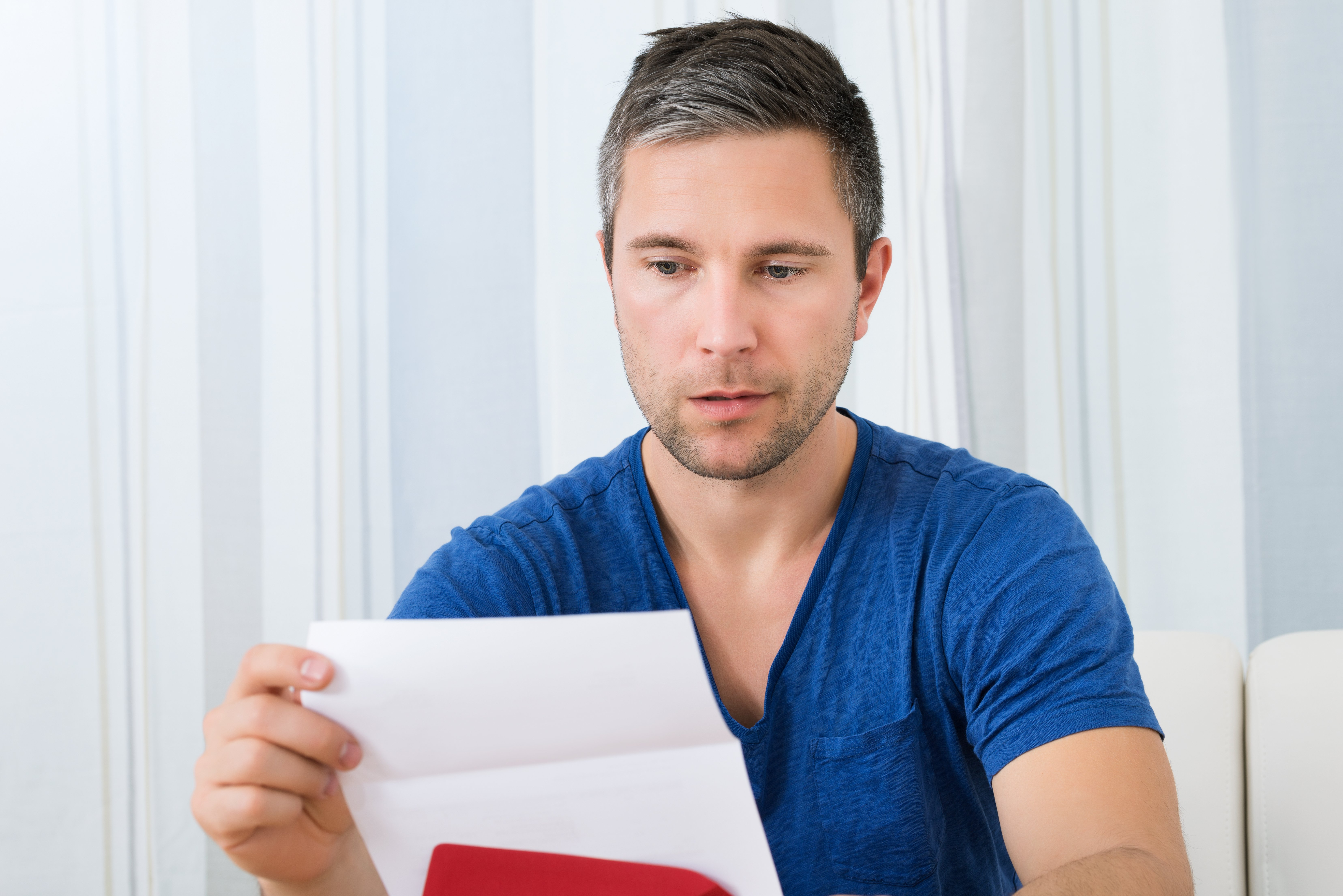 Portrait Of Unhappy Man Sitting On Sofa Reading A Piece of Paper | Photo: Shutterstock.com