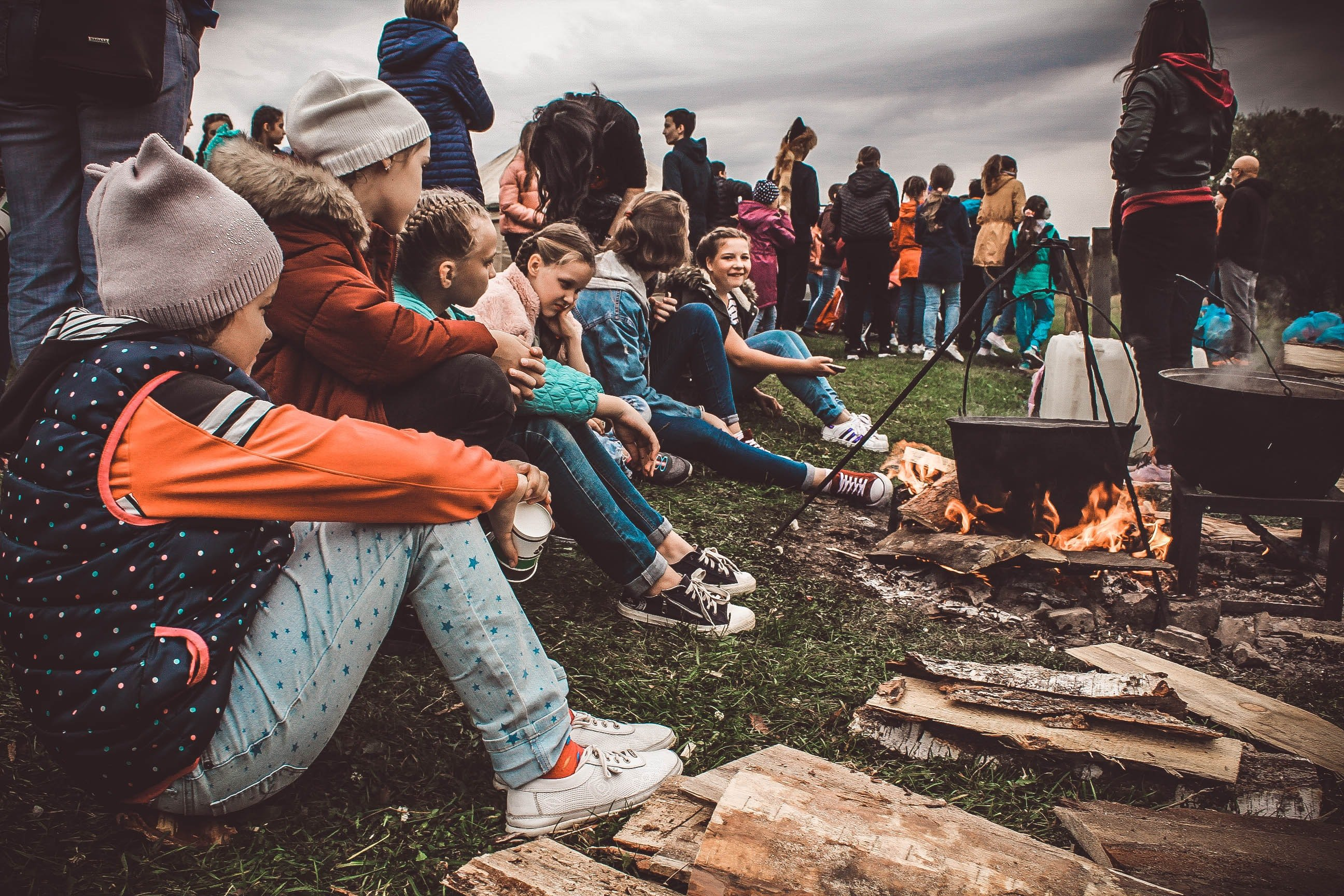 Group of kids sitting next to a fire pit   Source: Unsplash