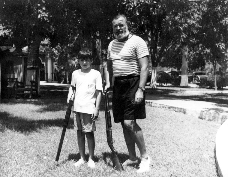 Ernest and Gregory shooting live pigeons at the Club de Cazadores in Cuba | Source: Wikimedia Commons/  Ernest and Gregory Hemingway in Cuba c1950, marked as public domain