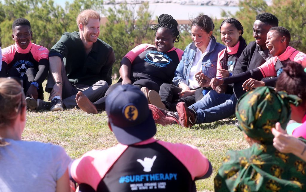 Prince Harry and Meghan join surf mentors and participate in a group activity as they visit Waves for Change, an NGO, at Monwabisi Beach.   Source: Getty Images
