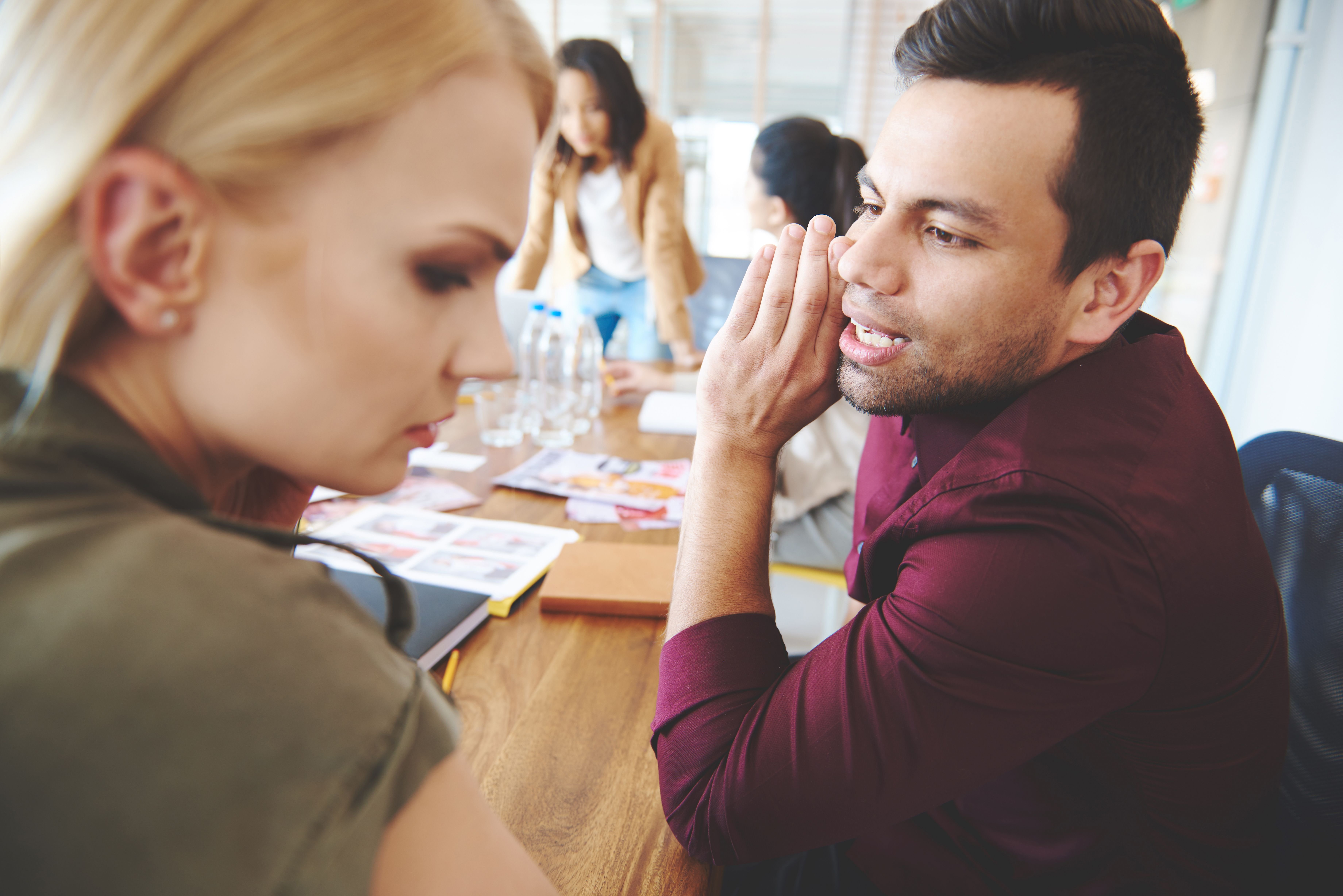 Co-workers whispering during a meeting at work. | Source: Shutterstock