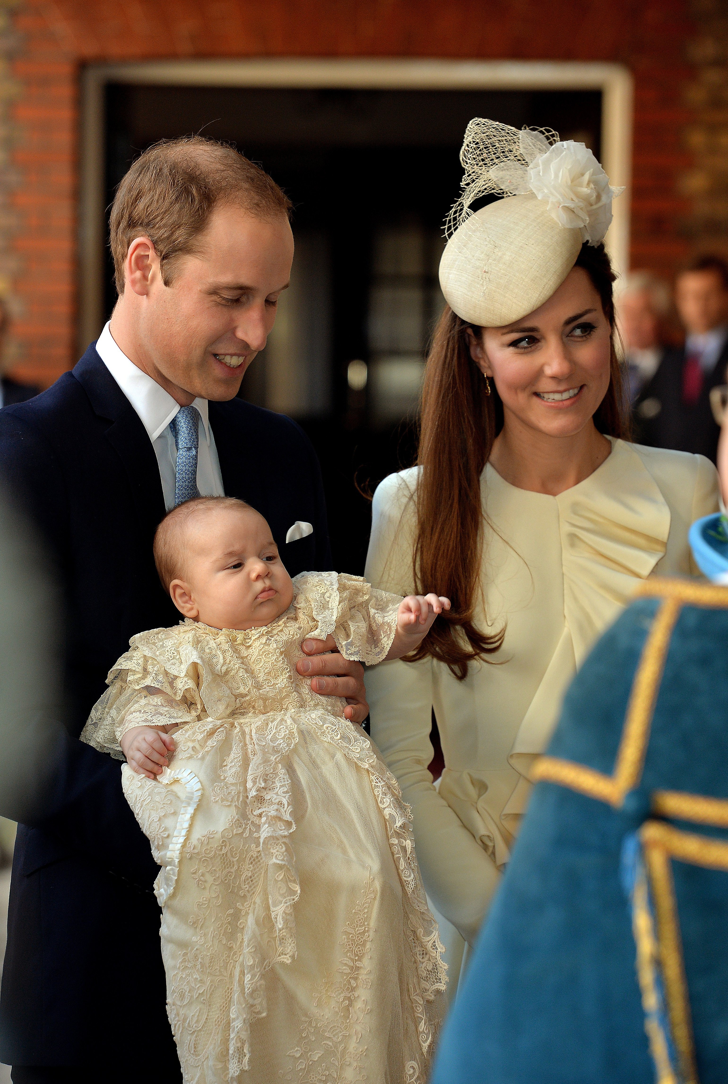 Prince George wearing the replice of the royal christening gown with Prince William and Kate Middleton at St James's Palace in London, England | Photo: Getty Images