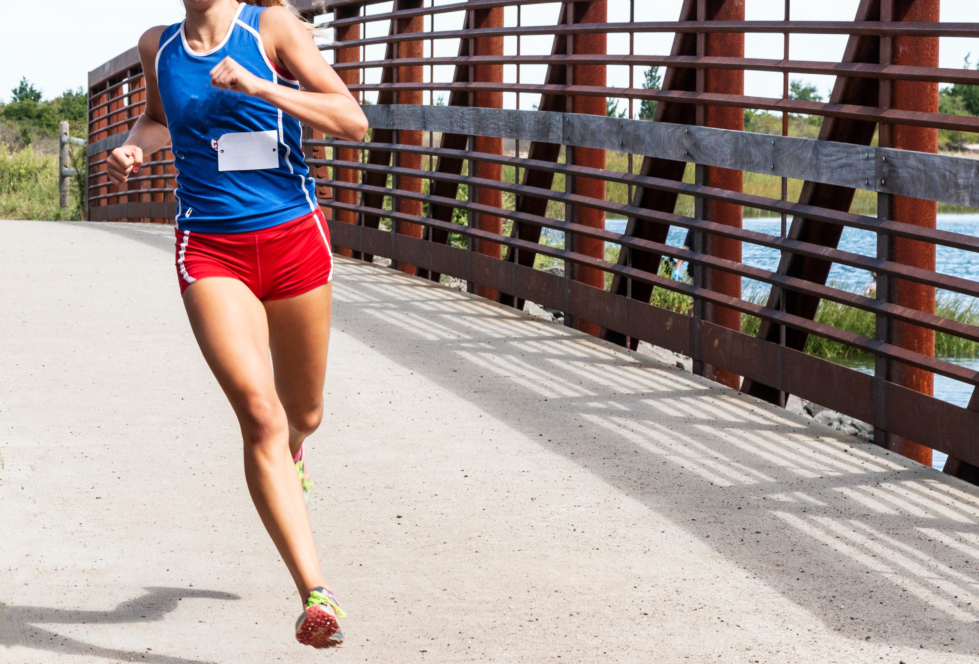 A high school cross country girl is running a race crossing a bridge wearing red shorts and blue racing top | Photo: Shutterstock