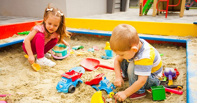 Two young children playing in a sandbox.   Photo: Shutterstock