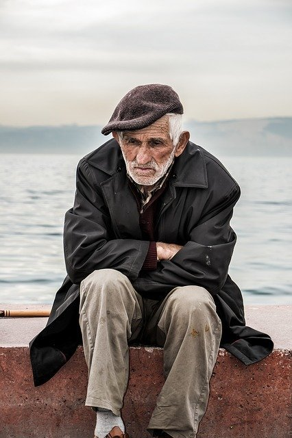 Older man sits by himself in front of the ocean looking down | Photo: PIxabay