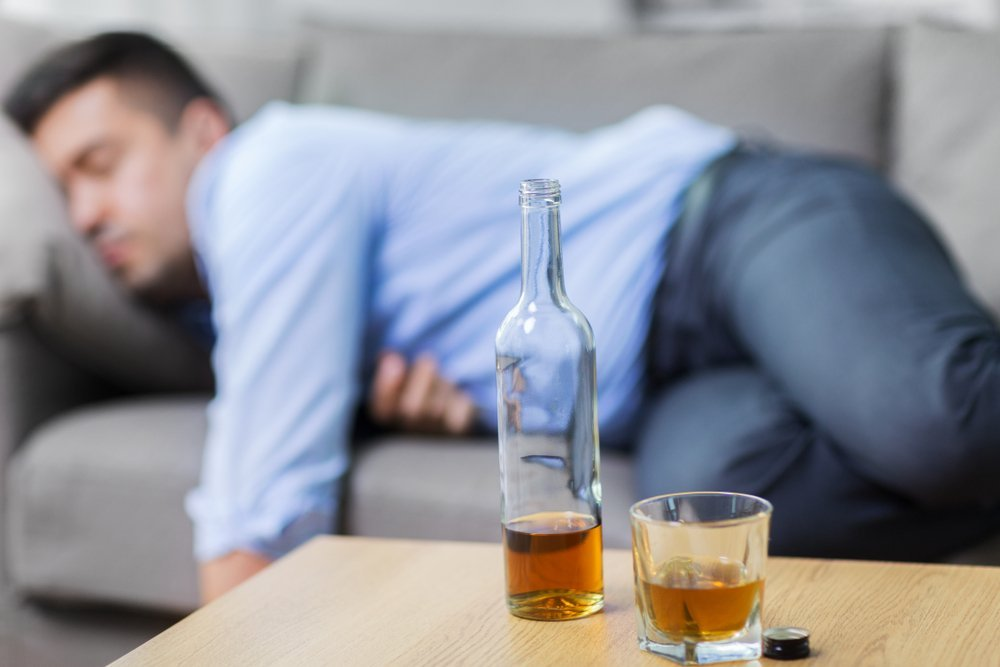 A photo of a sleeping drunk man with a bottle and glass of whiskey on table. | Photo: Shutterstock
