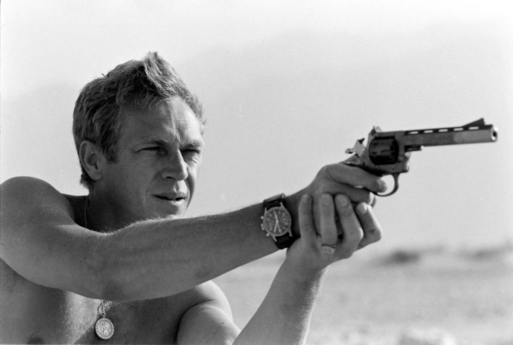 Actor Steve McQueen holding a pistol and taking aim in a desert area around Palm Springs, California in June 1963. | Photo: Getty Images