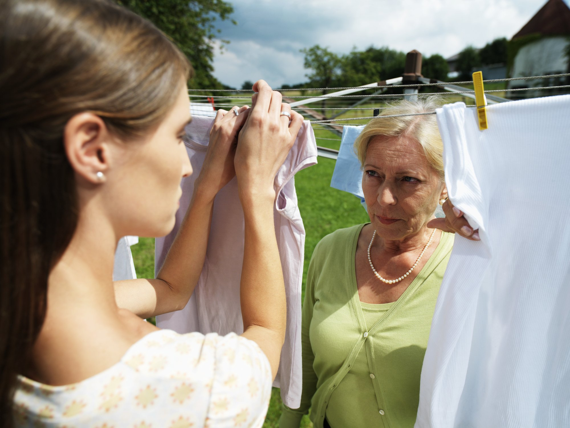Enraged mother-in-law stares at daughter-in-law who hangs out washed clothes   Photo: Getty Images