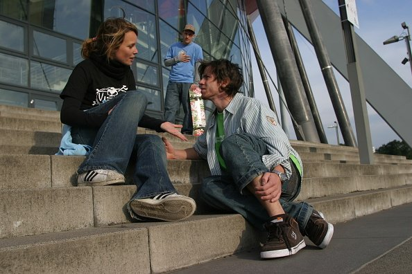 A young man sitting on the stairs having a discussion with a young lady | Photo: Getty Images