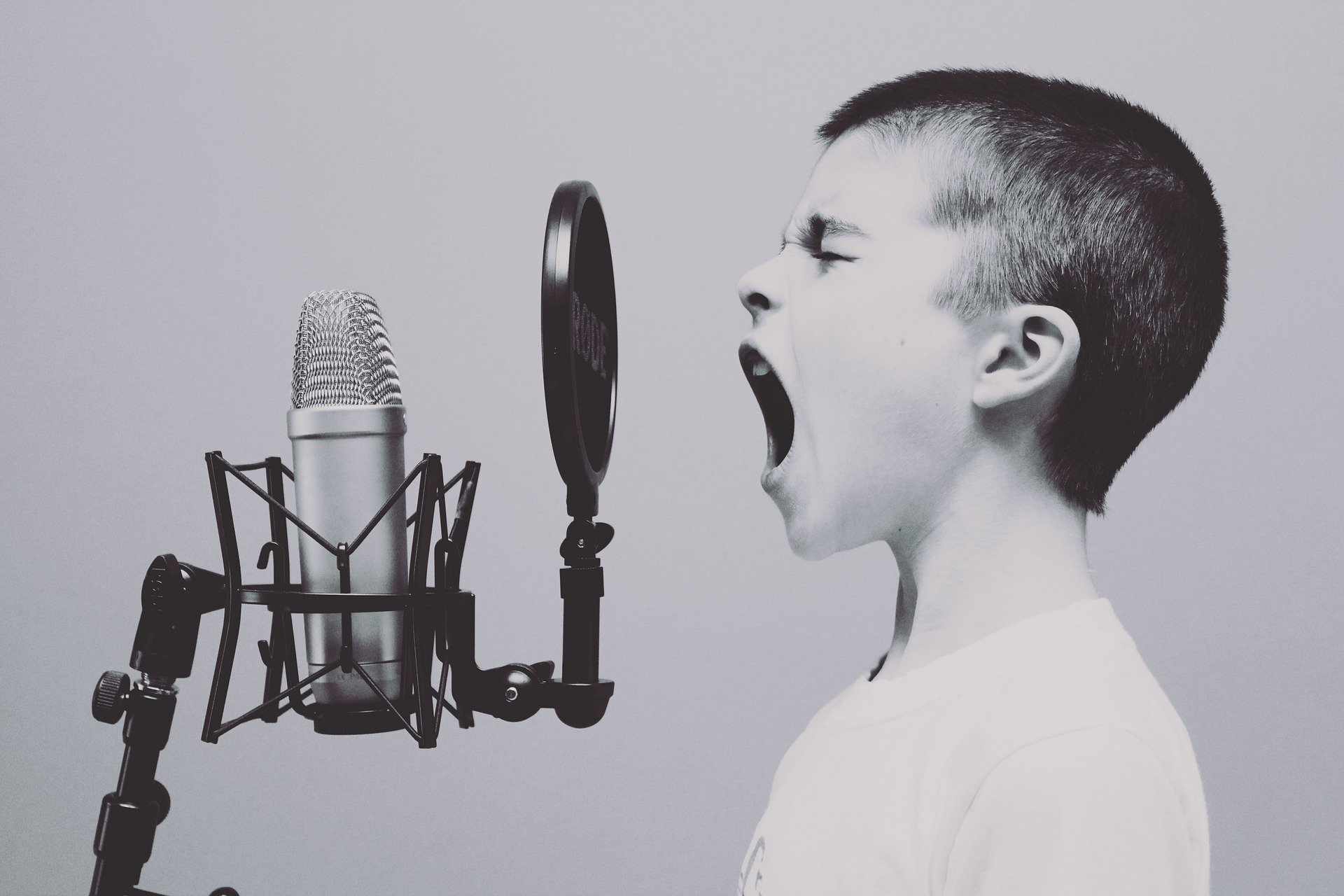 A young boy screaming into a microphone in a studio. | Source: Pixabay.