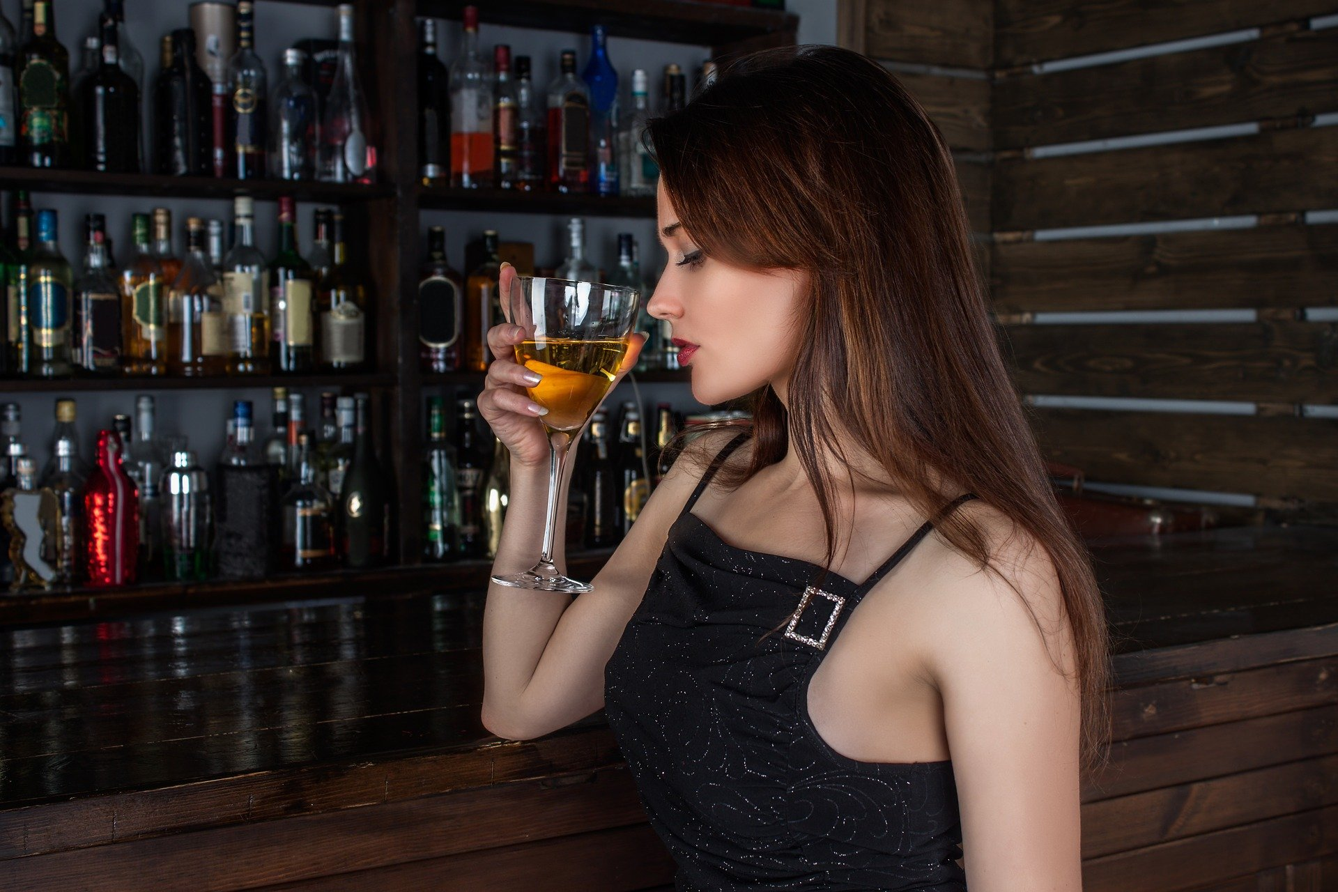 A beautiful young woman sitting alone at the bar drinking. | Photo: Pixabay