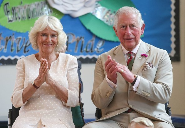 Prince Charles, The Prince of Wales and Camilla, the Duchess of Cornwall applaud after listening to the Aloud charity choir during a visit to White Rose Primary School  in Elliots Town.| Photo: Getty Images.