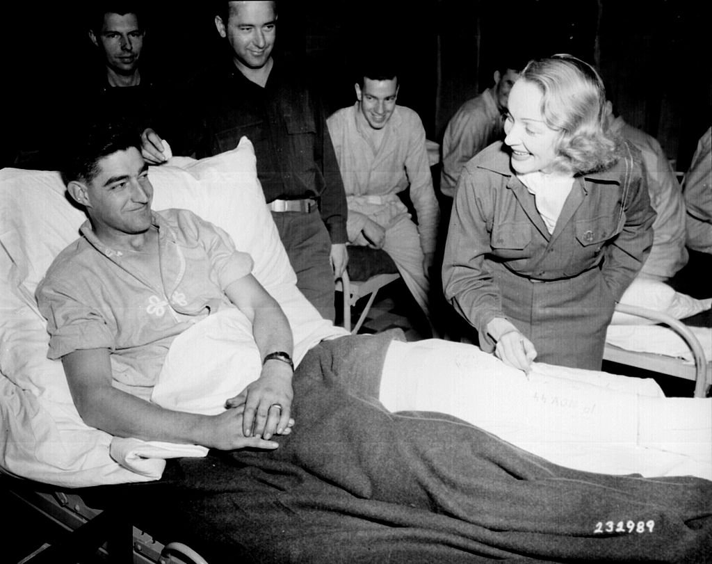 Marlene Dietrich autographs the cast on the leg of Tec 4 Earl E. McFarland of Cavider, Texas, on November 24, 1944 at a United States hospital in Belgium, where she has been entertaining the G.Is'. | Photo: NARA - 531330, WikiMedia