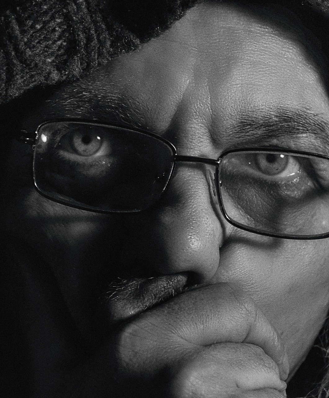 A black-and-white close-up image of a shocked man covering his mouth while wearing glasses and a hat | Photo: Pixabay/Alexander Krivitskiy