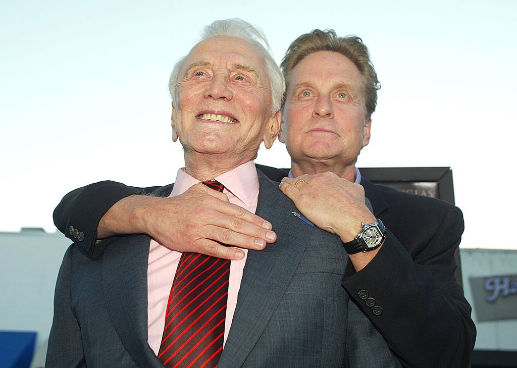 """Kirk Douglas and stands with son Michael Douglas as he hugs him from behind at the premiere of """"It Runs In The Family"""" on April 7, 2003, in Los Angeles, California 