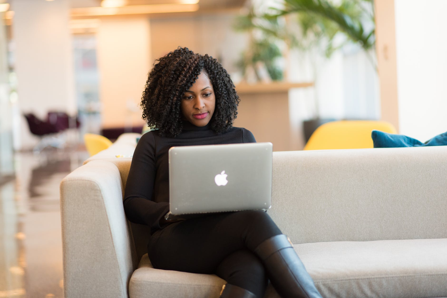 Woman sitting on a sofa and using her laptop   Source: Pexels