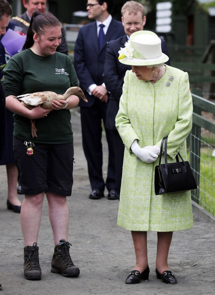 Queen Elizabeth II with keeper Maia Gordon during a visit to Gorgie City Farm | Photo: Getty Images