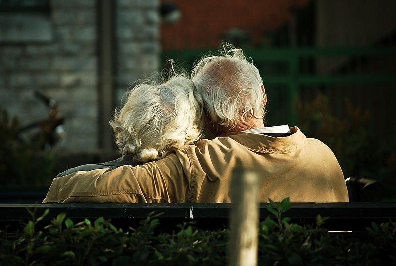 Pareja de ancianos abrazados en una banca. | Foto: Wikimedia Commons