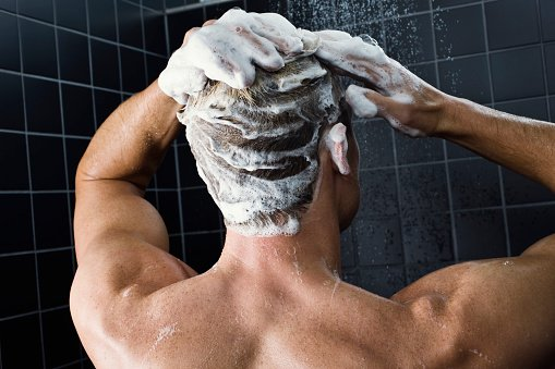 Photo of a man washing his hair with a shampoo | Photo: Getty Images