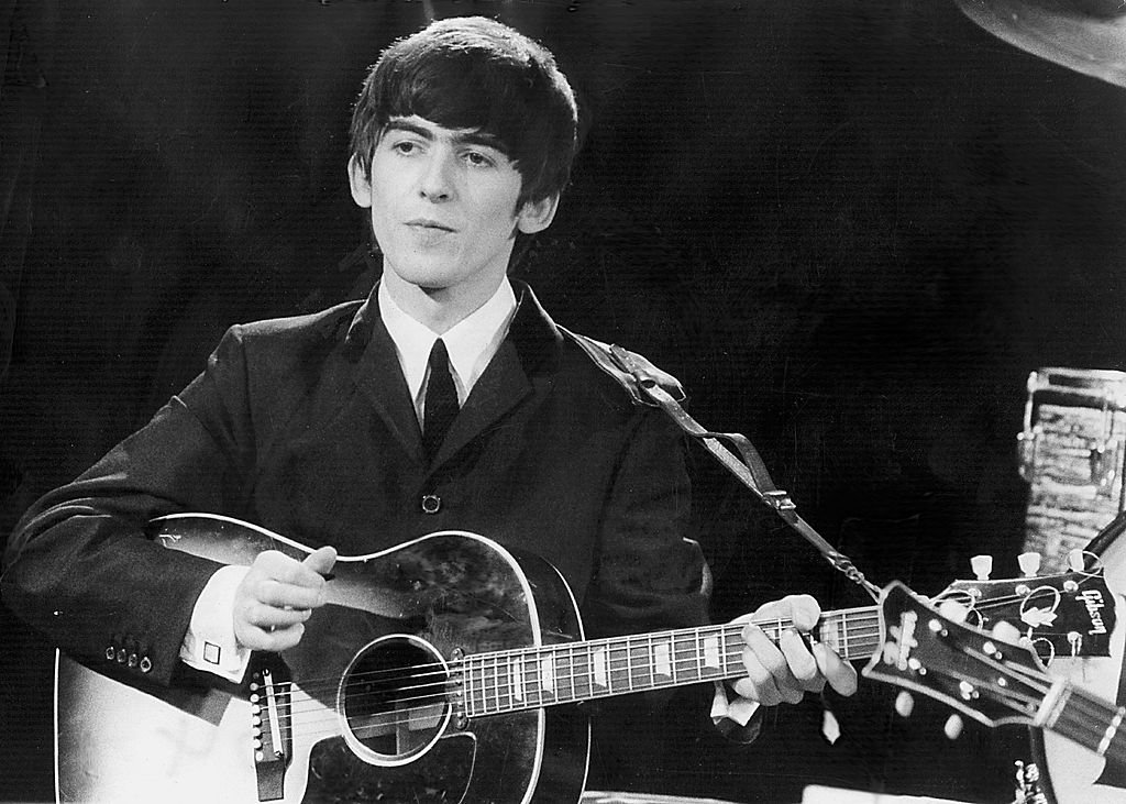 Beatles guitarist and singer George Harrison performs December 3, 1963 during a concert.  | Getty Images / Global Images Ukraine
