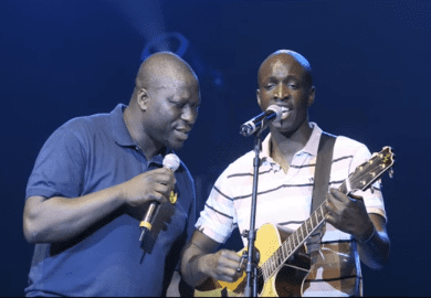 Mouss Diouf chante avec un guitariste. | Photo : Youtube / Europe 1