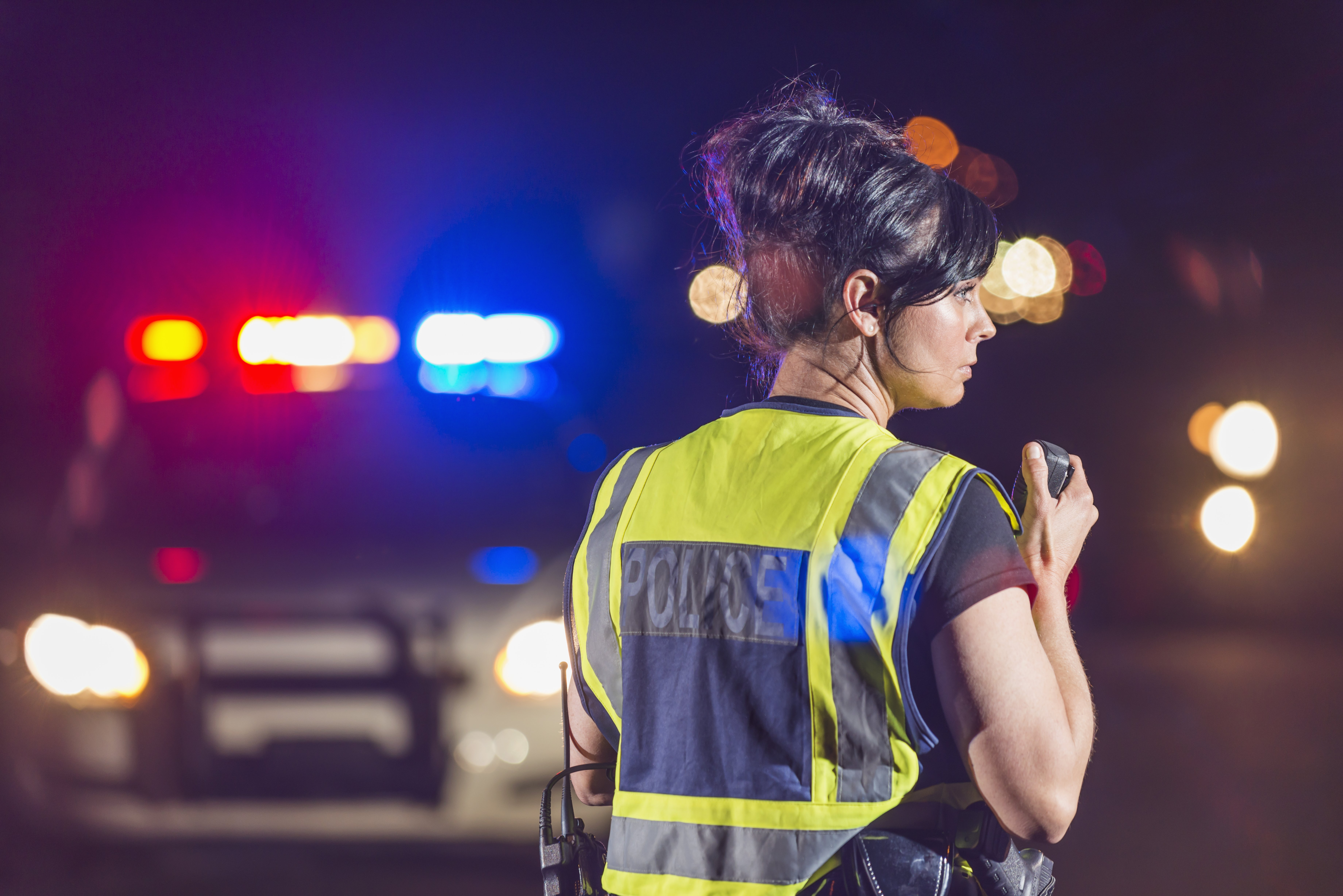 Rear view of a female police officer standing in the street at night, talking into her radio. Her patrol car is in the background with the emergency lights illuminated. She is wearing a yellow safety vest|Photo: Getty Images