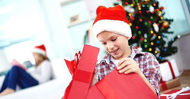 An excited boy opening his gift | Photo: Shutterstock