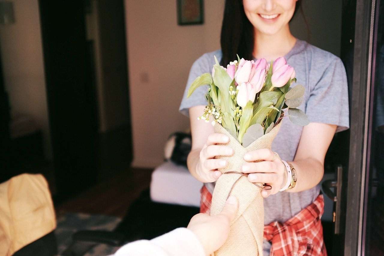 Woman receiving a bouquet of flowers. Image credit: Pixabay.