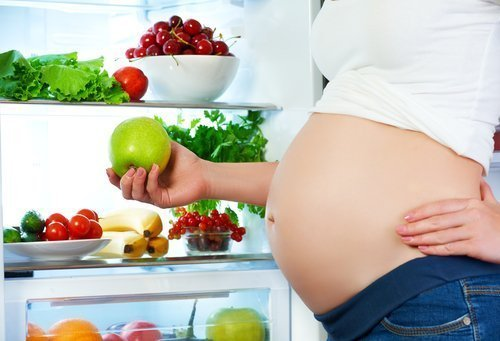 Pregnant woman standing near refrigerator with fruits and vegetables. | Photo: Shutterstock