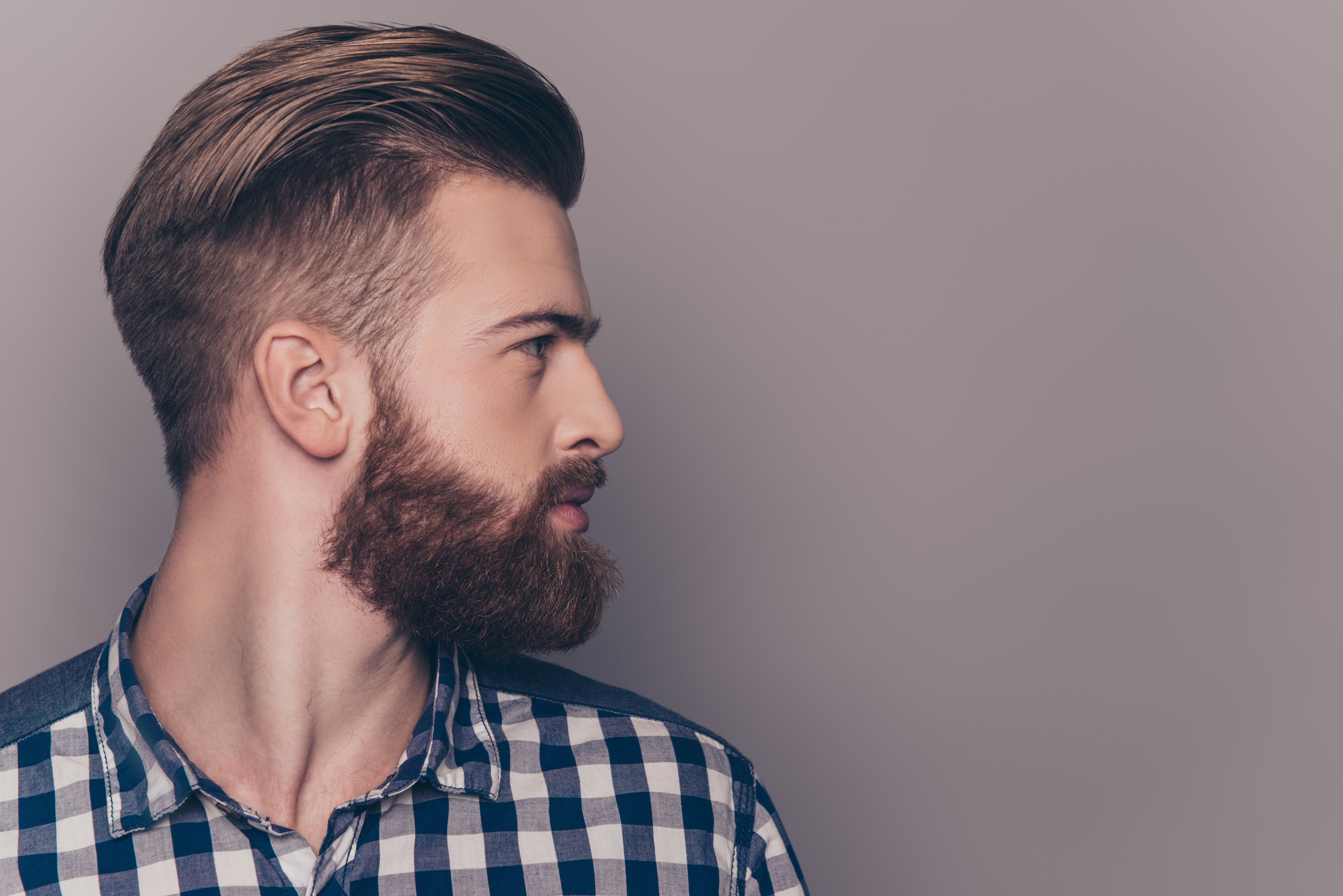 The profile of a man with a beard, wearing a blue plaid t-shirt. | Photo: Shutterstock