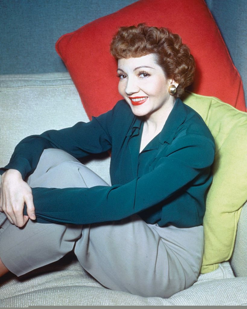 French-born US actress, Claudette Colbert, wearing a blue blouse and grey trousers in a studio portrait, circa 1950 | Photo: Getty Images