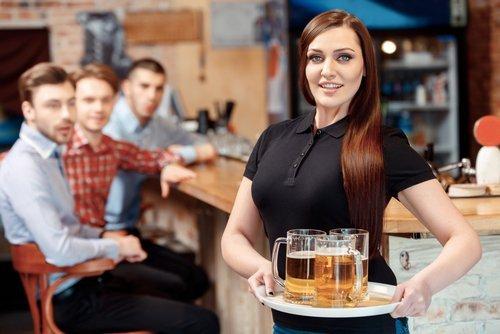 Une belle serveuse tenant un plateau avec des verres à bière pendant que les jeunes hommes la regardent avec étonnement | Photo : Shutterstock